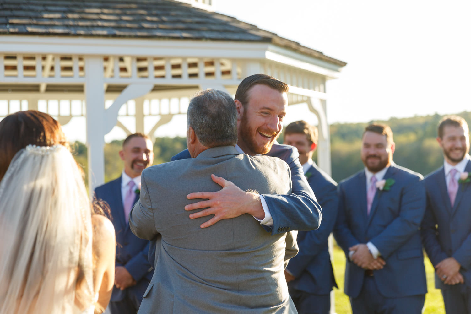 Father of the bride and groom hug at beginning of ceremony