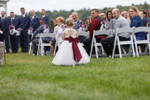 Flower girl walking down the aisle at outdoor ceremony