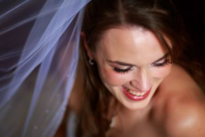 Wedding day portrait of a happy smiling bride. The veil in the background with soft window light streaming onto the bride
