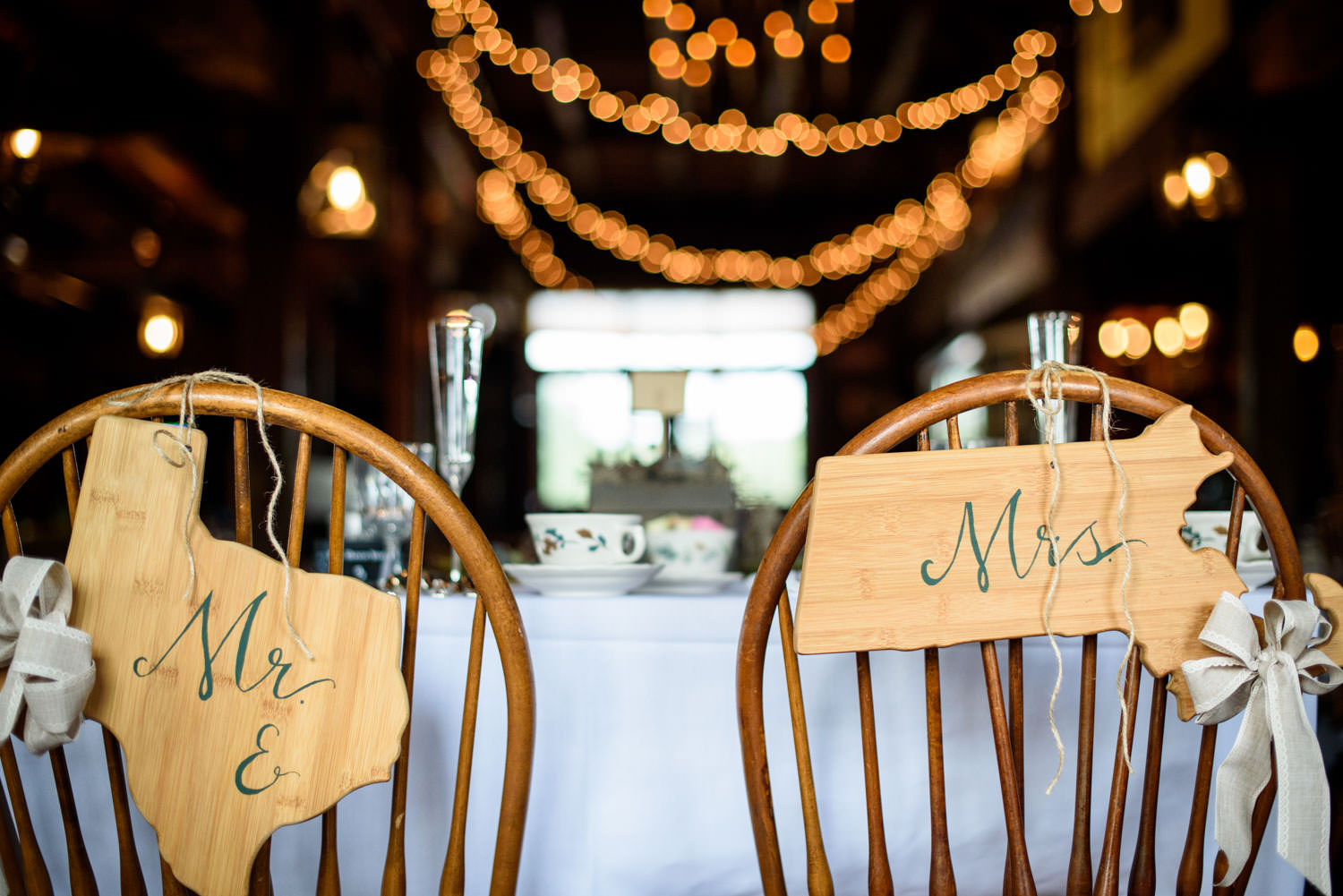 Mr. and Mrs. signs on chairs with twinkle lights in background in reception