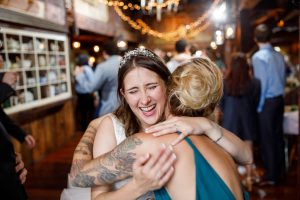 Happy bride hugging sister in law during wedding reception