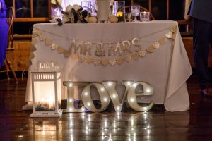 Sweetheart table with Love sign in the foreground.