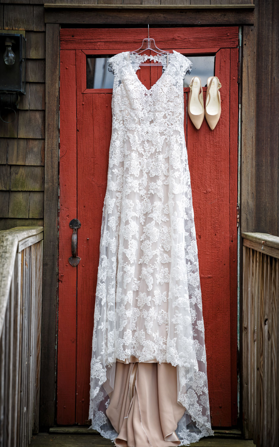 Brides wedding shoes and dress hanging outside on the red barn door at the Salem Cross Inn. This photo works well with the red of the door contrasting the brides off white dress.