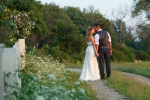 Bride and Groom leaning for a kiss on path