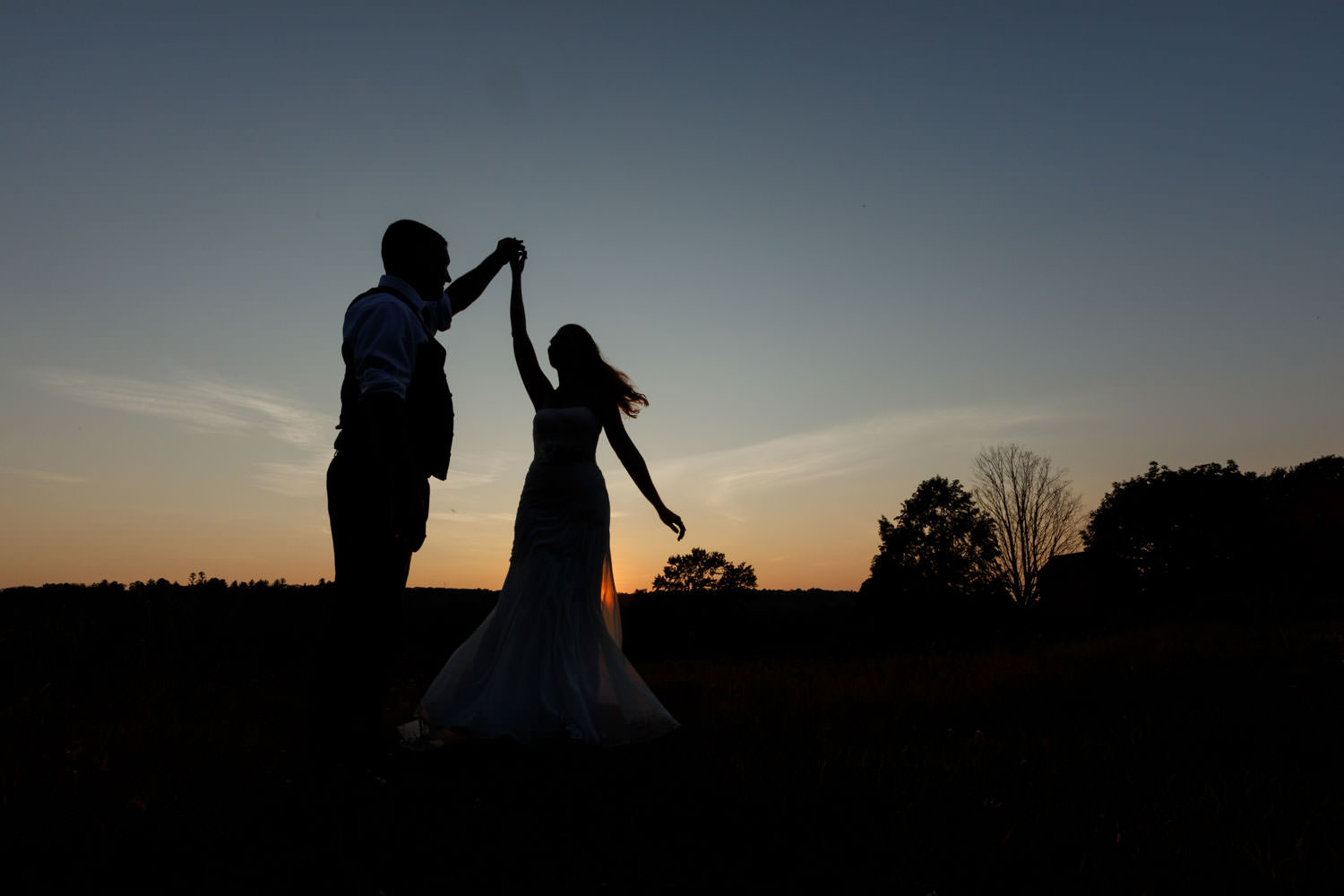 silhouette of groom twirling bride at sunset