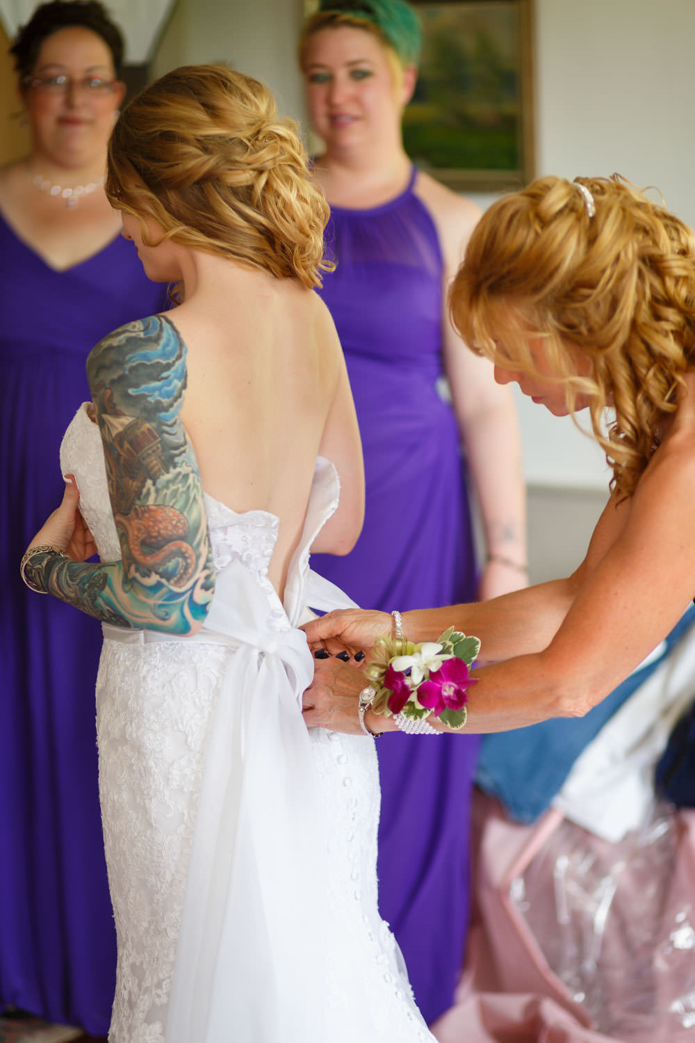 The brides mother zipping up her wedding dress. Purple bridesmaids dresses in the background in the bridal suite. The bride has intricate tattoo on her left arm.
