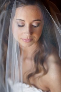 Beautiful wedding day portrait with the brides eyes closed. Shooting through the veil giving a soft look to her portrait.