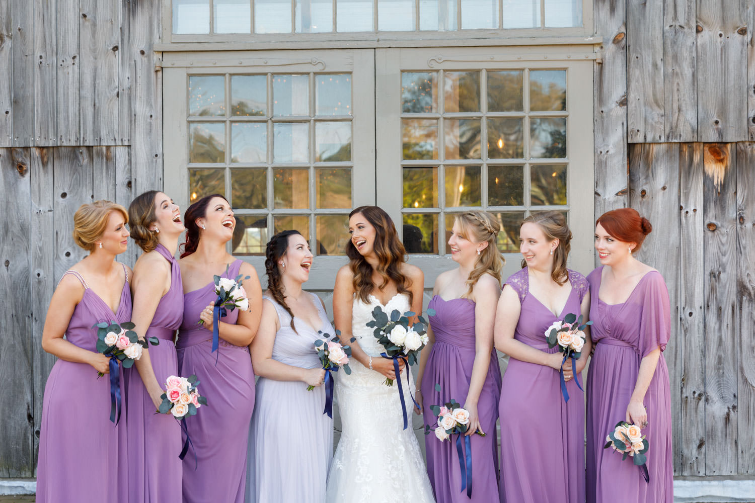 Bride with bridesmaids laughing in front of the barn.
