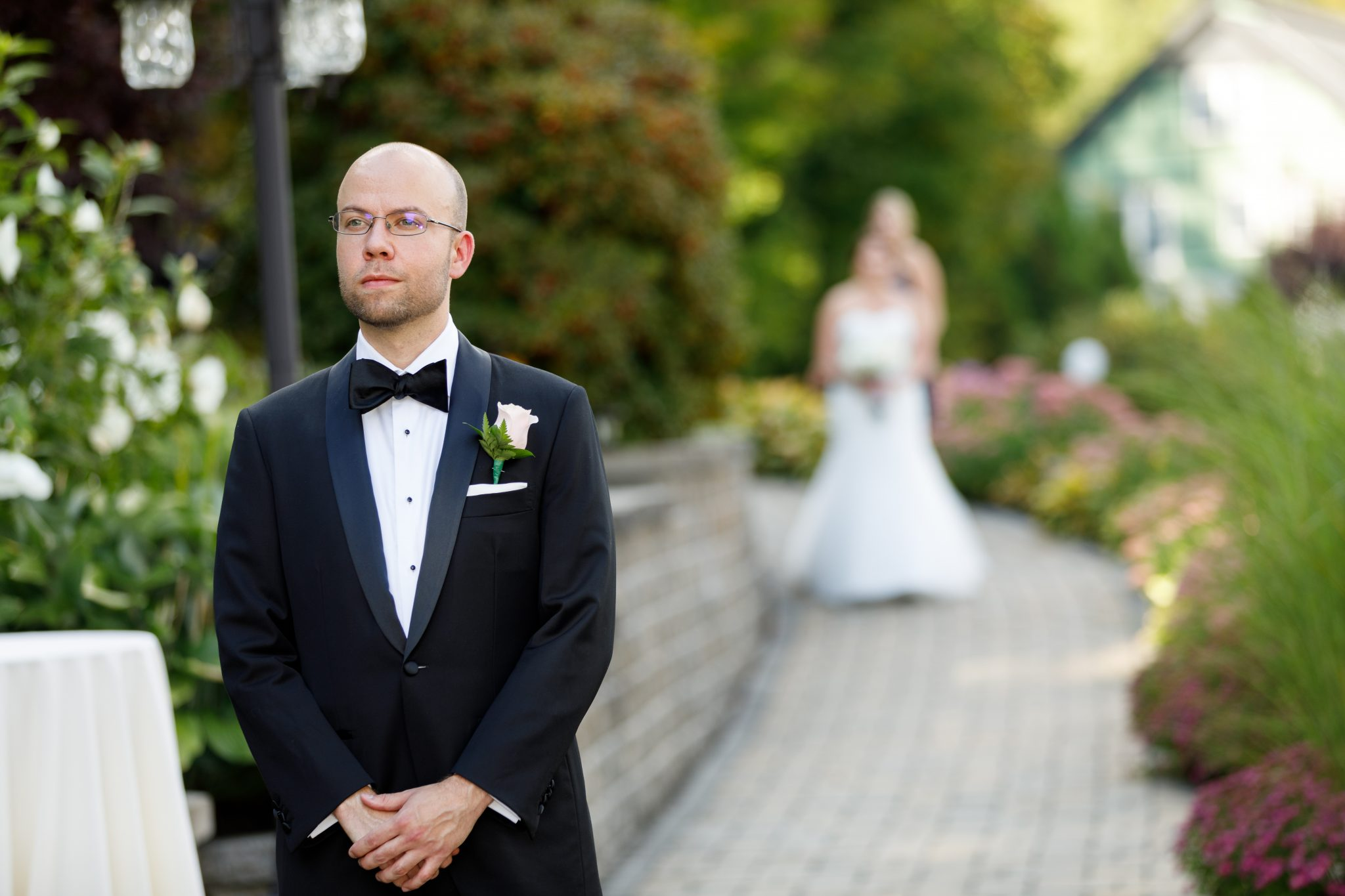 Groom in foreground of first look photo at the Mountain Rose Inn