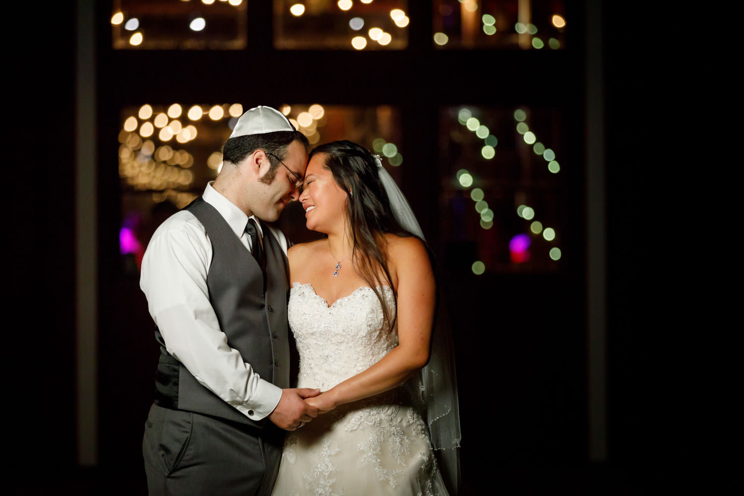 Night time photo with jewish bride and groom with twinkle lights blurred in background