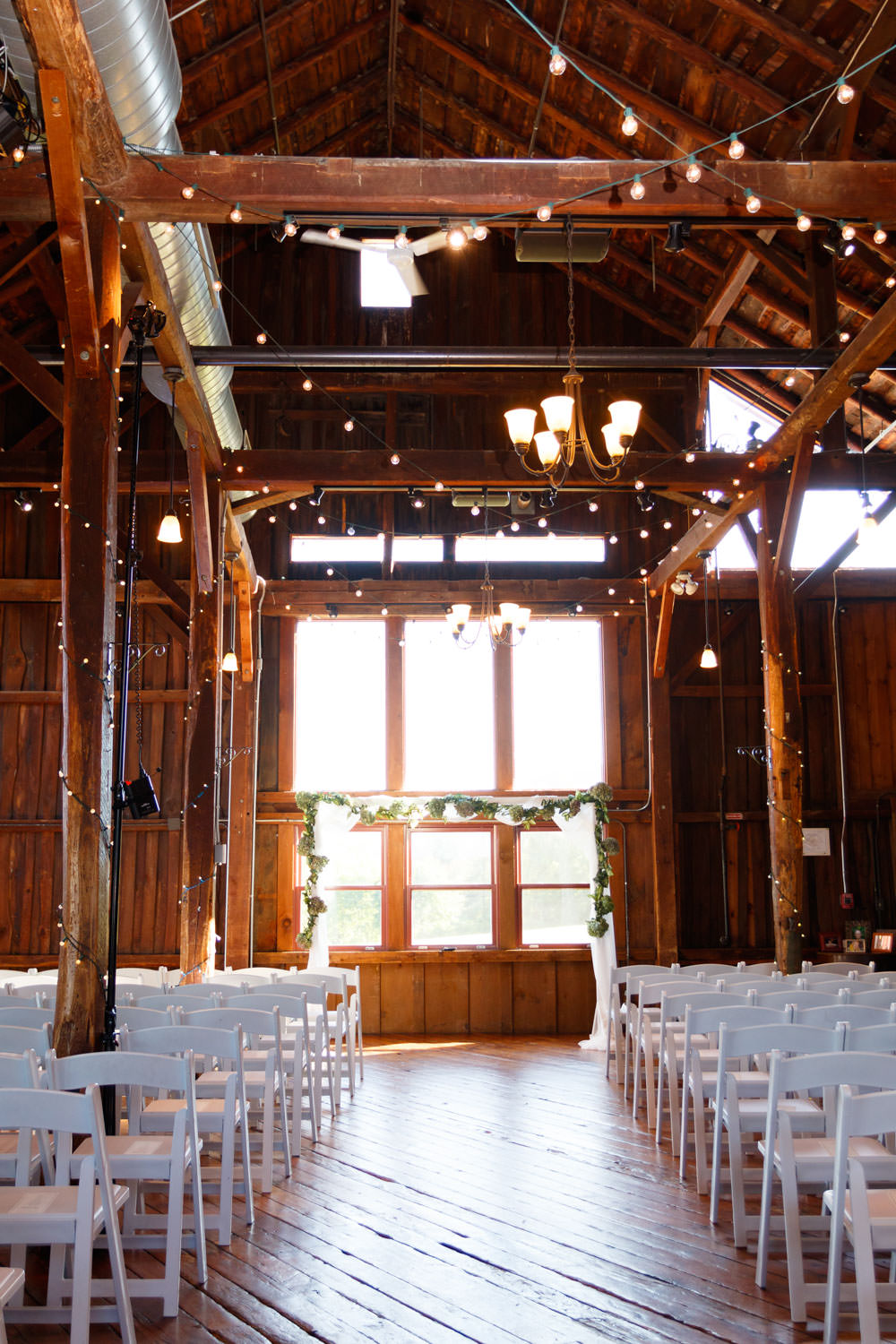empty ceremony space setup with white chairs inside barn