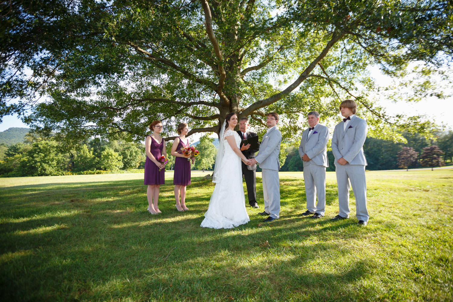 Outside ceremony by the large tree at the red barn