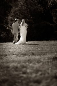 Black and White photo of the bride and groom walking away in a field at the red barn