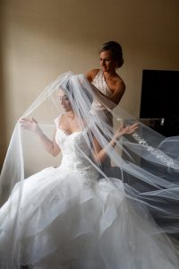 Elegant photo of bridesmaid helping bride with veil. Veil is delicately draped over bride.