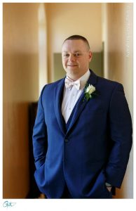 Groom Portrait in blue suit and pink bow tie at church
