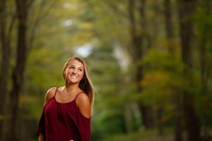 Senior girl photo in path in woods with blurred backgroud