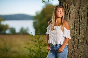 Senior photo leaning against a tree with quabbin reservoir in backgroud