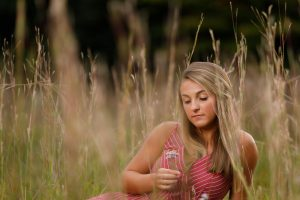 Senior photo in Hanks Meadow holding flower