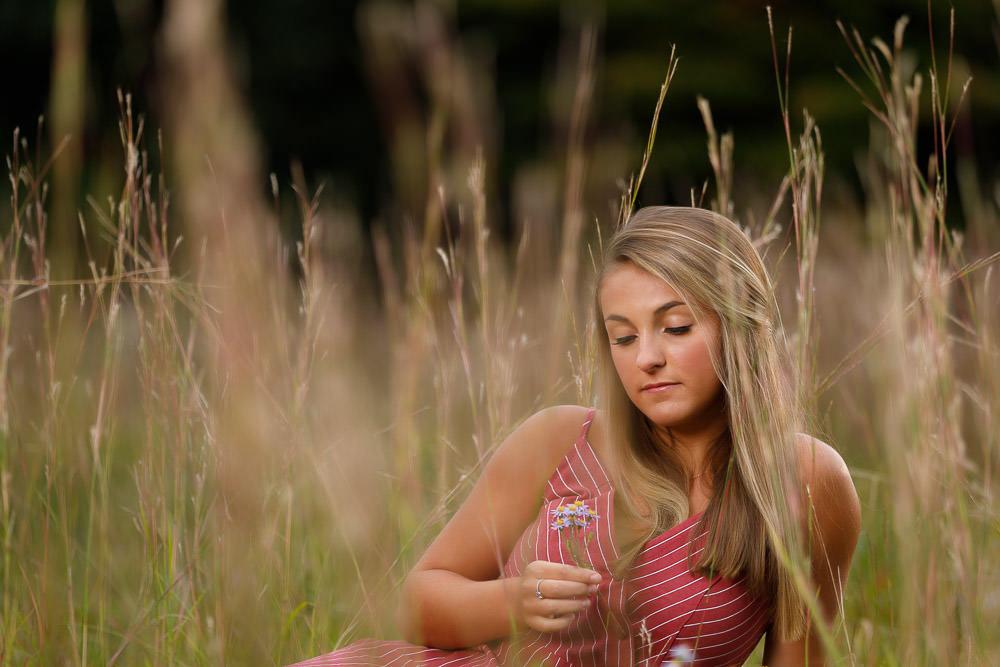 Senior photo in Hanks Meadow holding flower