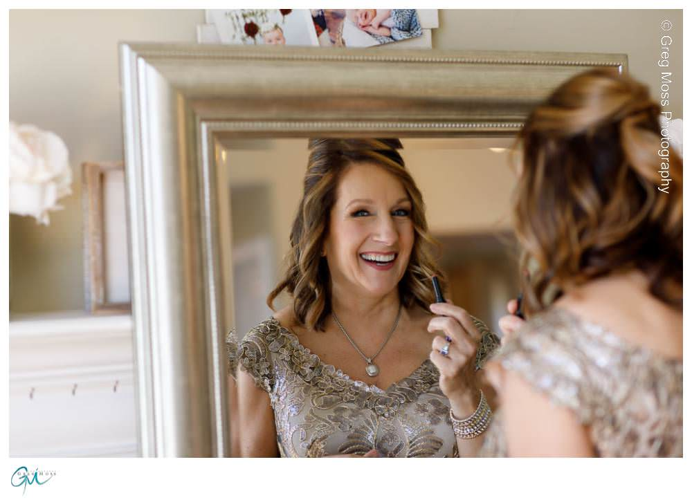 Mother of the bride laughing in the mirror while