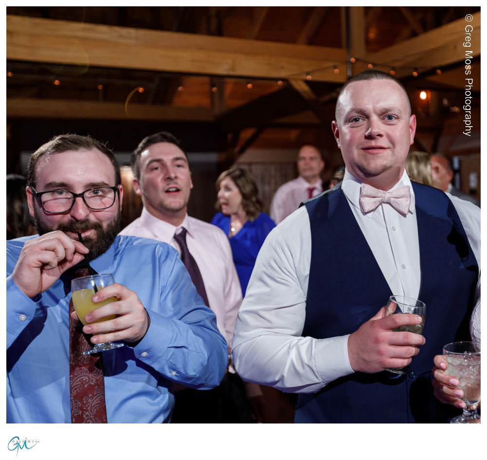 Groom and friend on dance floor with drink and straw