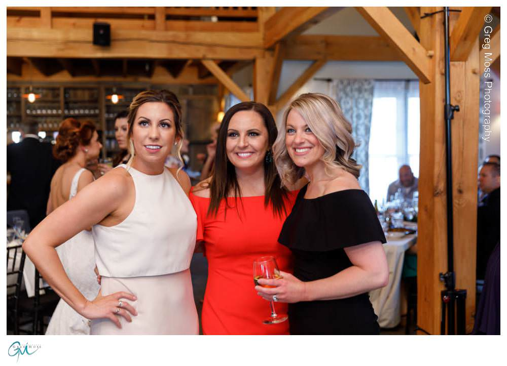 Maid of honor with friends on dance floor in barn