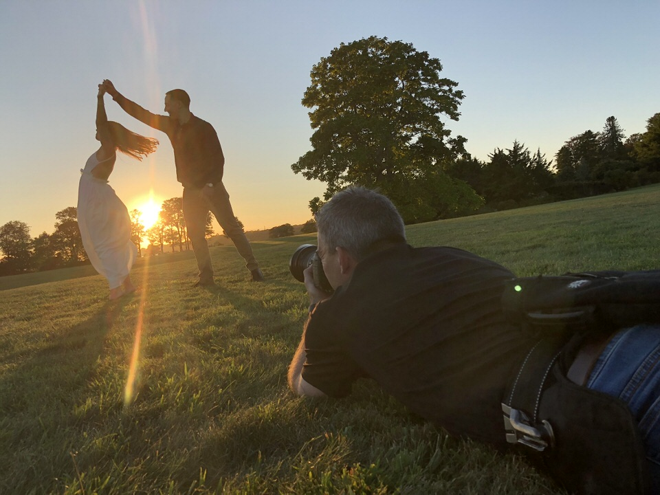 Photographer laying on the ground taking sunset photo of couple while guy twirls girl