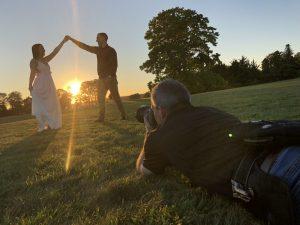 Photographer laying on the ground taking sunset photo of couple while guy twirls girl