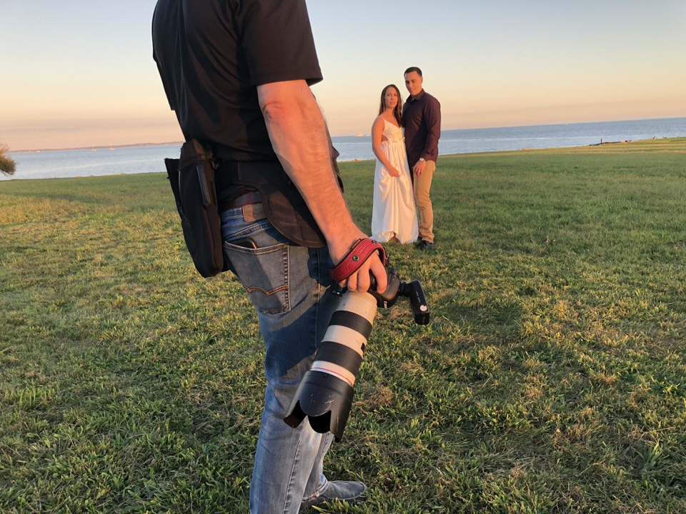 Engaged couple with photographer and camera in foreground