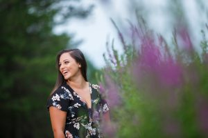 High School Senior Girl laughing with purple flowers in the foreground