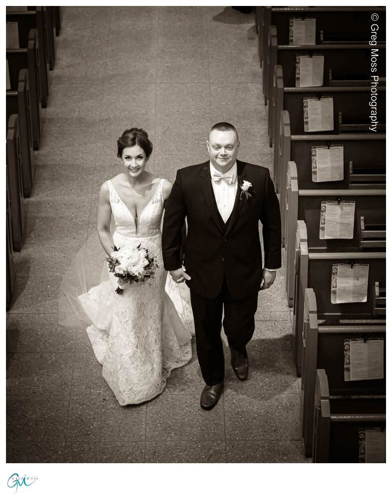 Black and White photo of Bride and Groom walking down the aisle
