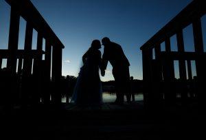 Silhouette of wedding couple on dock at Sturbridge Host Hotel
