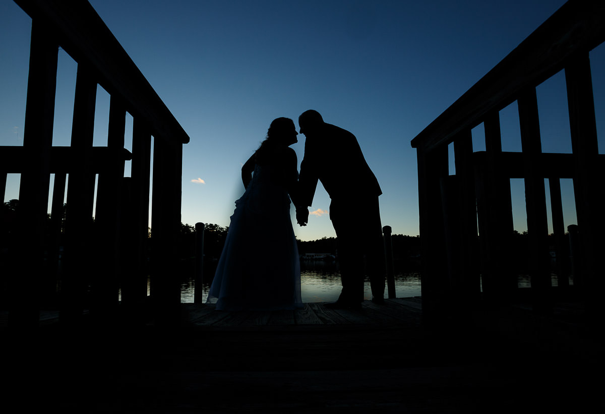 Silhouette of wedding couple on dock at Sturbridge Host Hotel