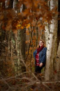 Senior portrait in the fall leaning against a birch tree