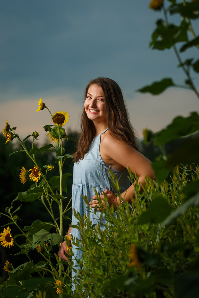 senior girl with blue dress in sunflower field