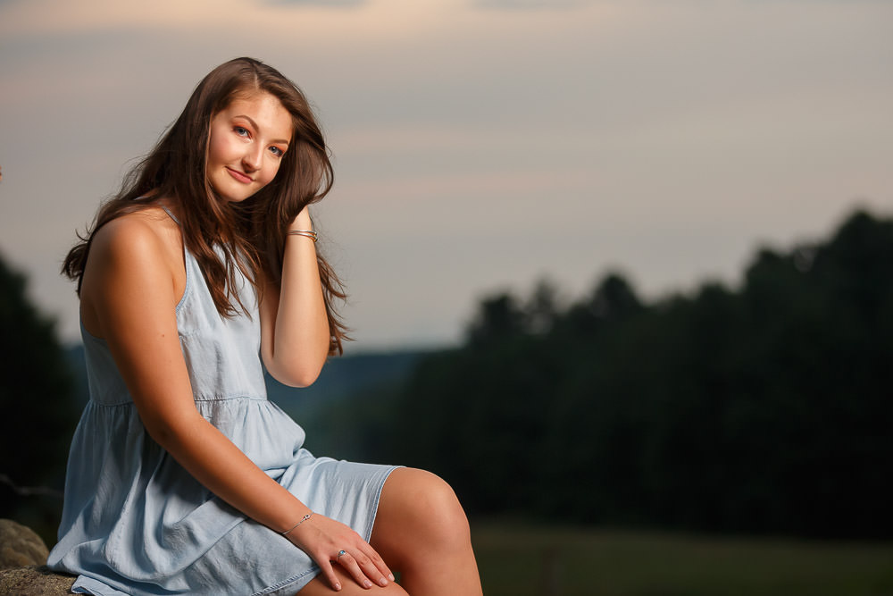 Sunset photo with high school senior girl and pretty blue dress with hand in hair.