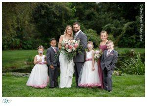 Family portrait on wedding day with bride and groom and their 5 kids