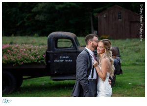 Zukas HIlltop Barn Truck with flowers and Groom Kissing bride in front