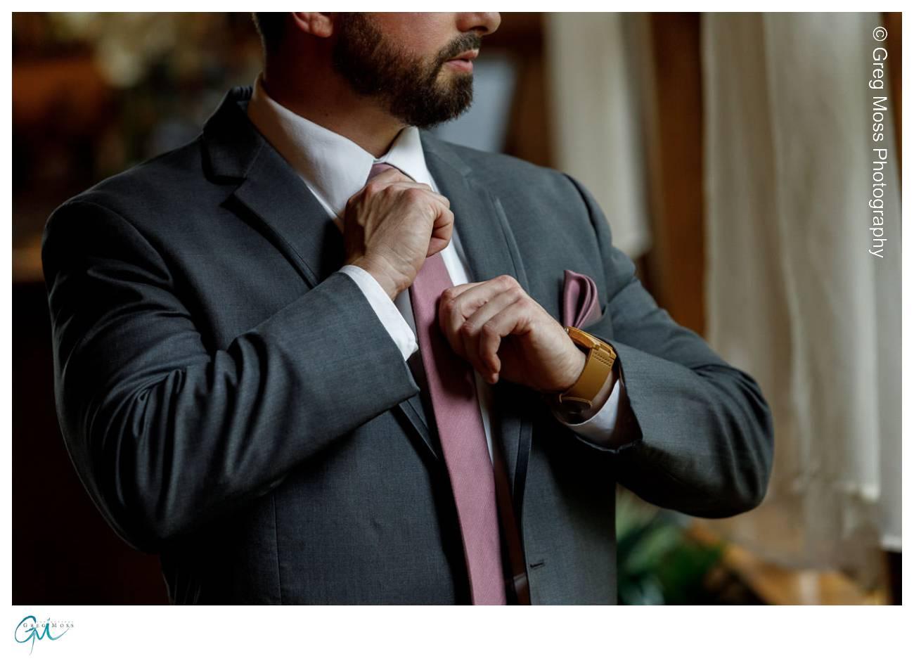 Groom adjusting maroon tie