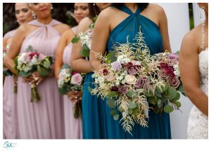 Maid of honor holding brides bouquet during ceremony