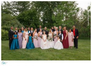 Large family photo at wedding in grassy area