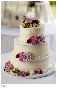 White wedding cake with purple flowers