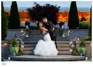 Bride and groom dipping on stairs with tent in background