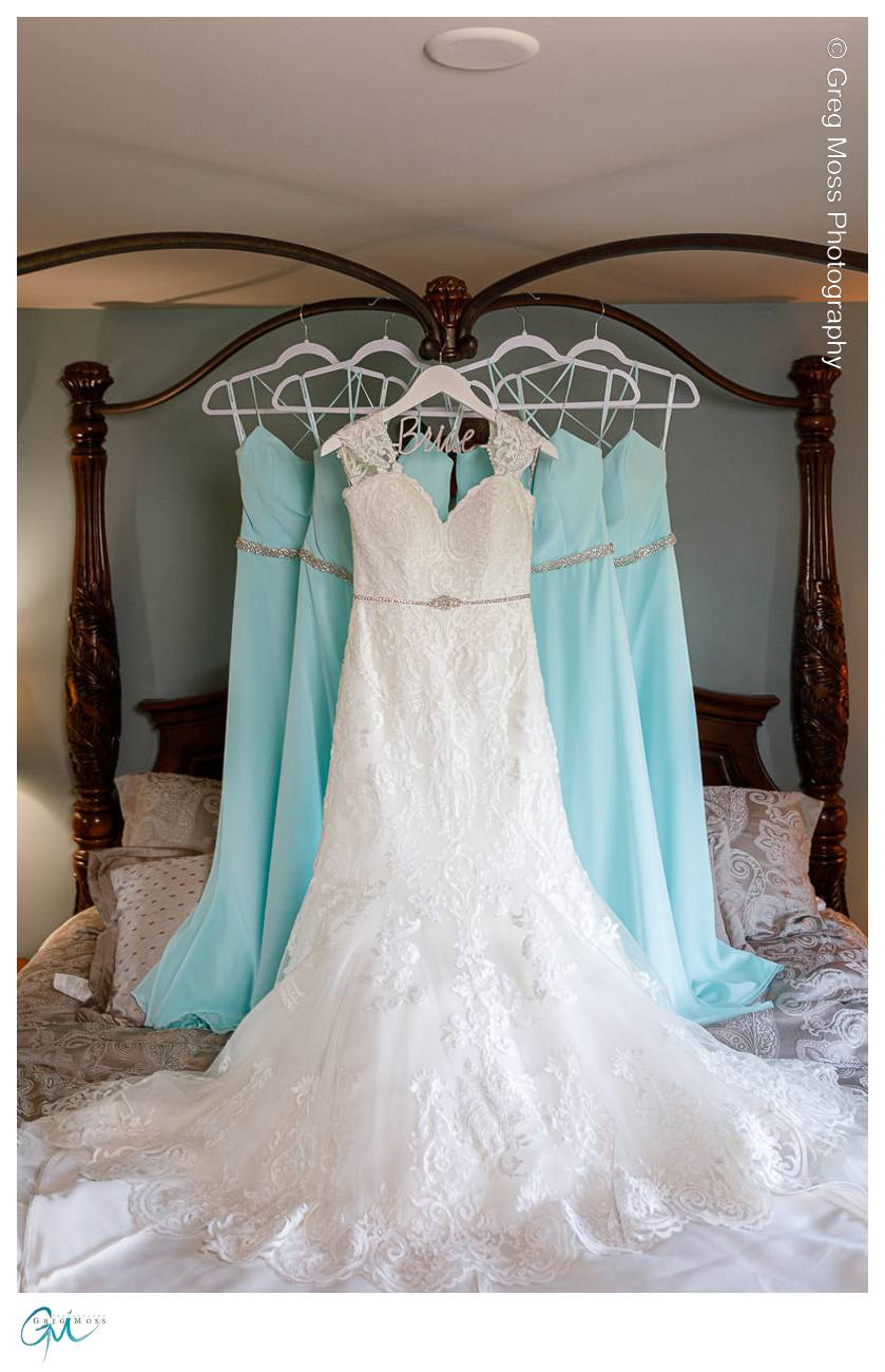 Brides dress and bridesmaids dresses hanging from four post bed