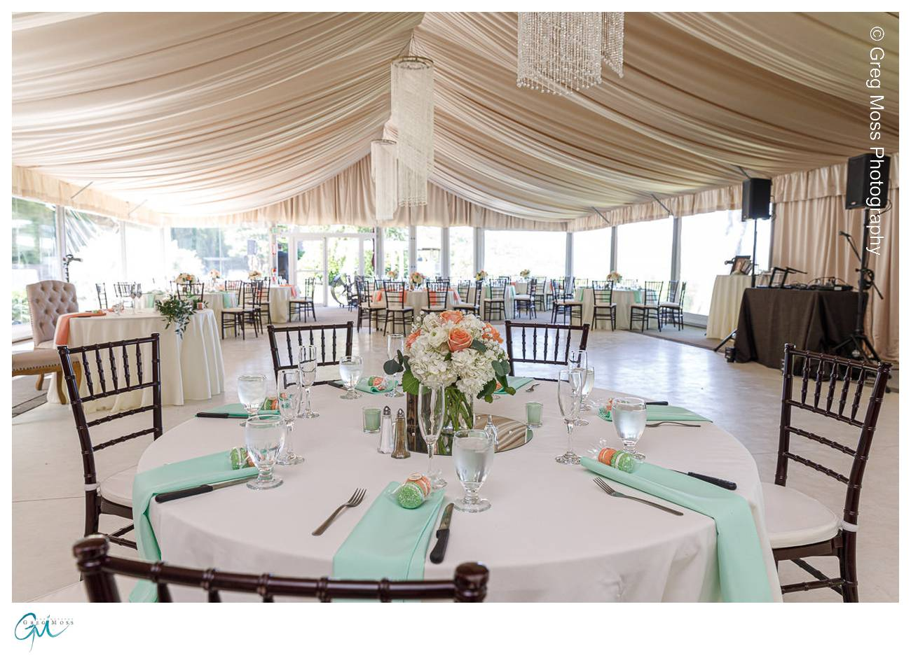 Photo inside tent with tables set with flower centerpieces and mint colored napkins