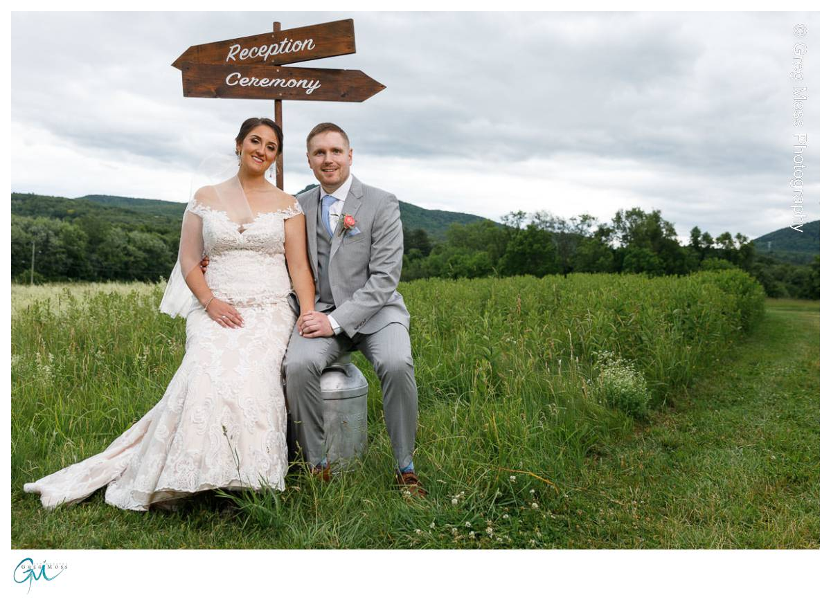 Bride and groom sitting under reception and ceremony signs