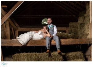 Bride laying across Groom sitting in loft of barn
