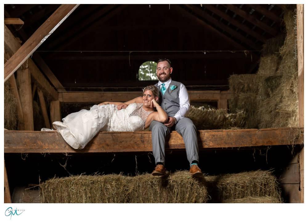 Bride laying across Groom sitting in loft of barn