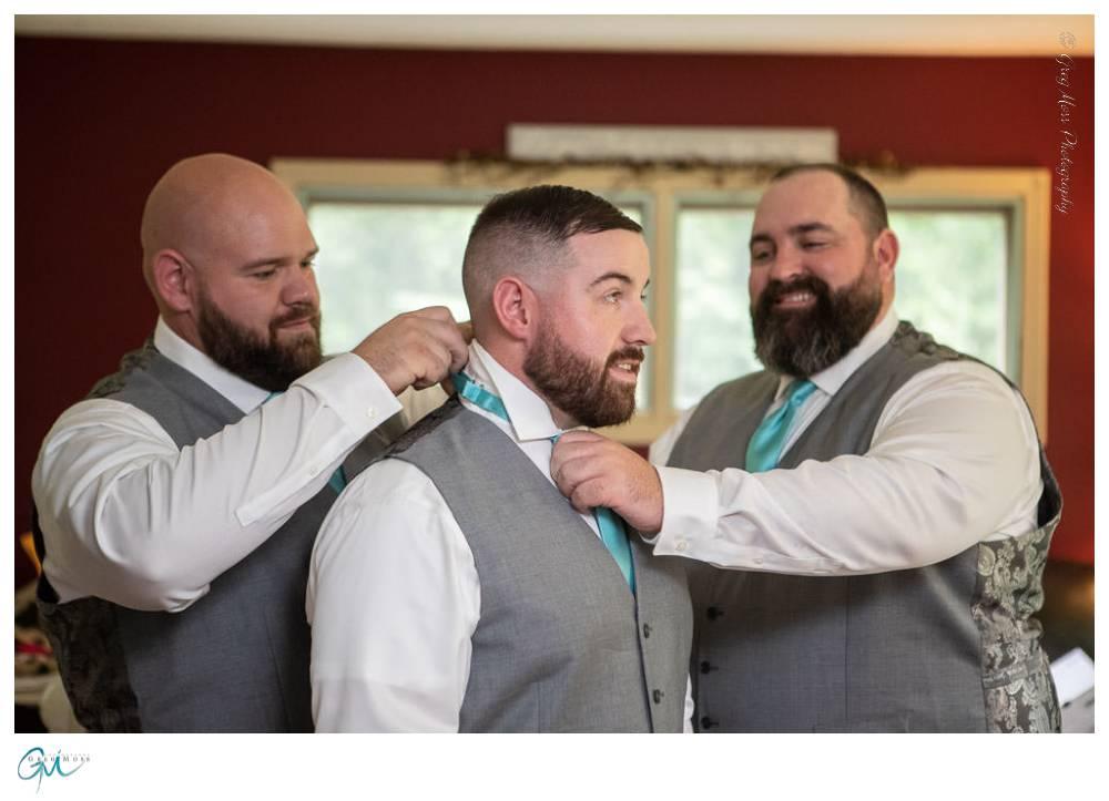 Groomsmen helping groom with his tie