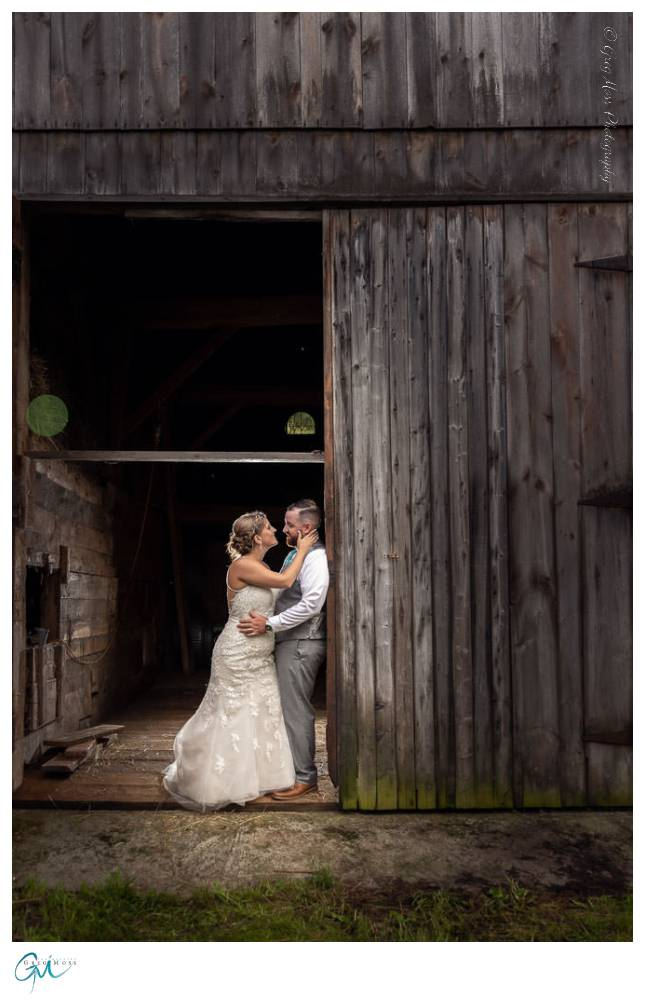 Bride and Groom leaning against barn.
